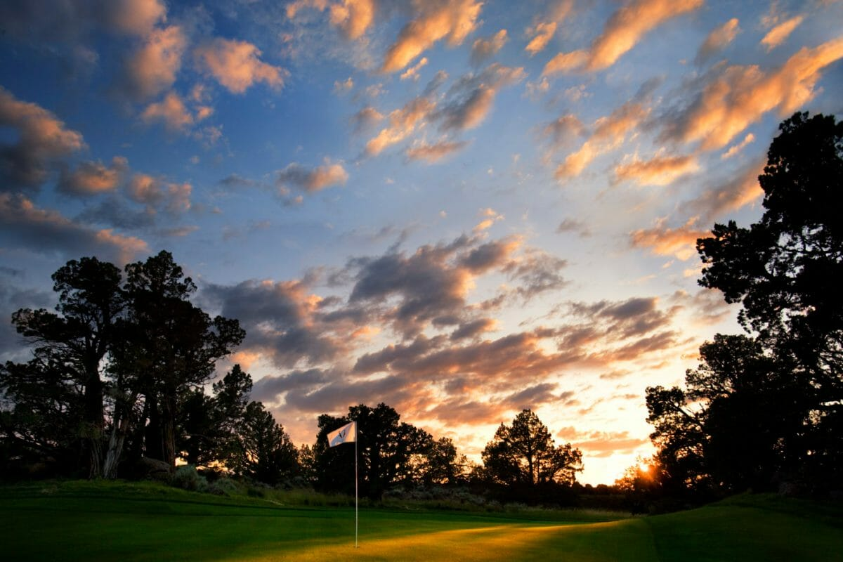 Setting sun contrasts golden sky with dark earth at Pronghorn Resort