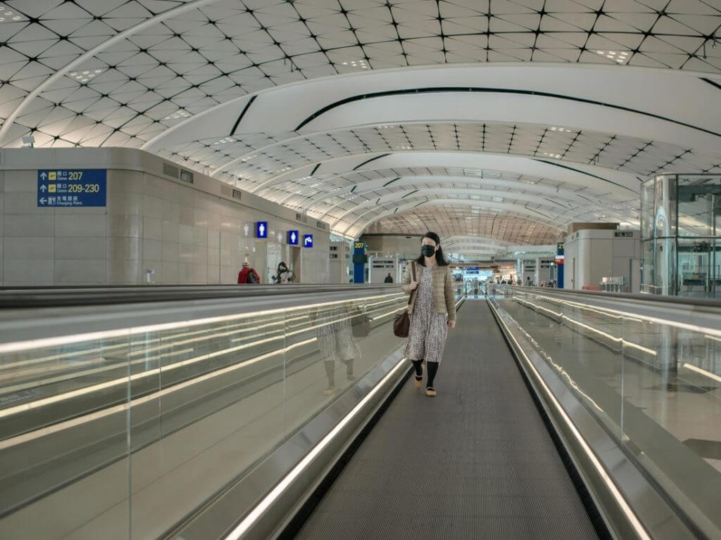 Woman in face mask in empty airport terminal