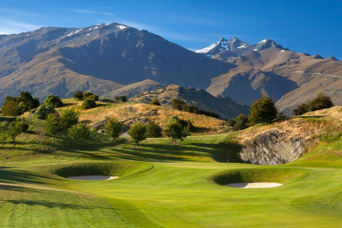 A fairway and green has a mountainous backdrop