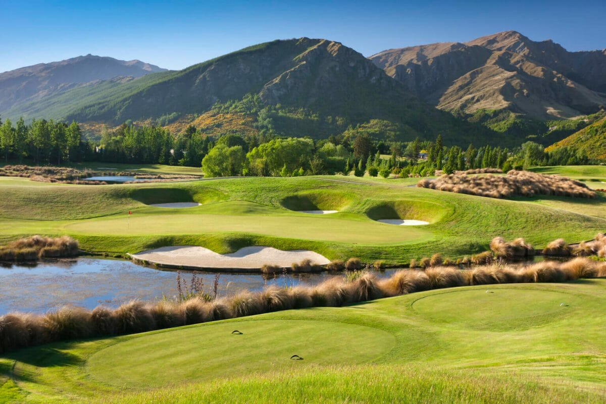 Dragonfly lake resides between the fifth and sixth golf holes with mountains behind