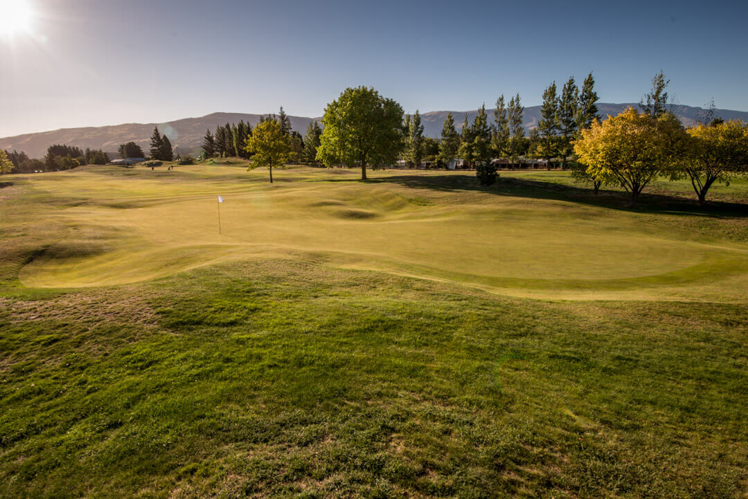 Tenth green and fairway lined with native trees