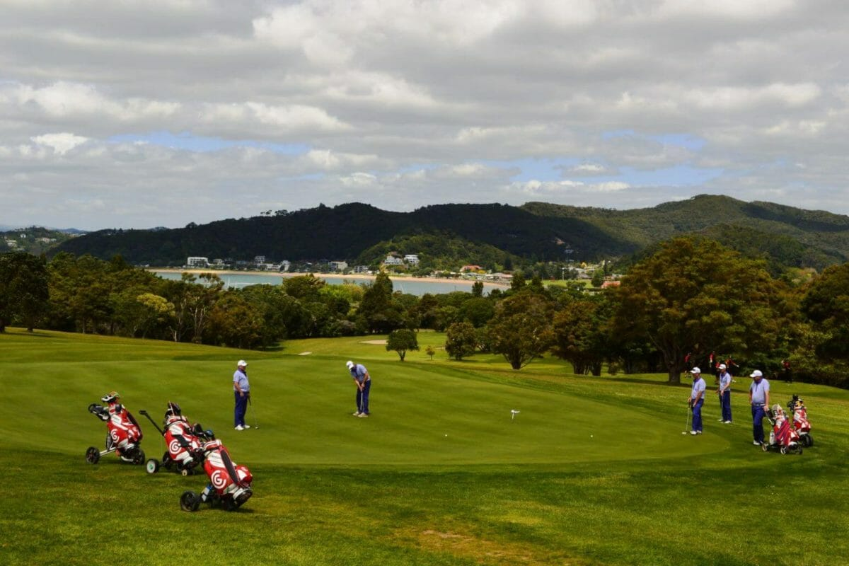 Golfers putt on a green with views over nearby Russell