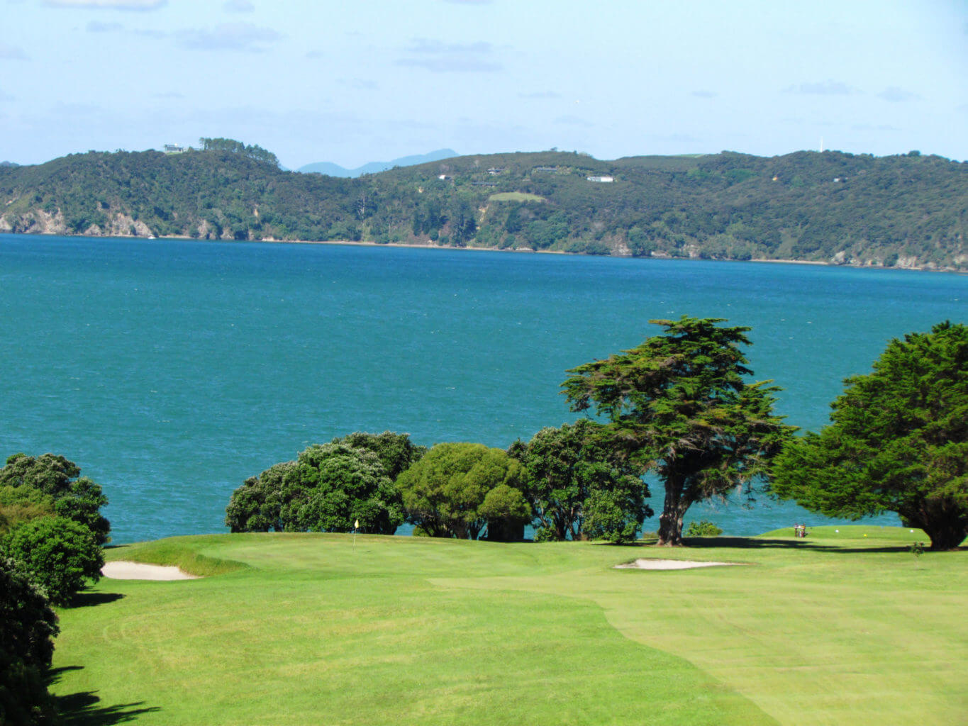Golf hole leads downhill with Bay of Islands view