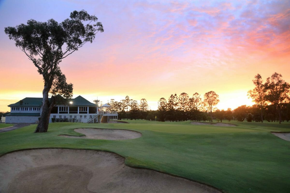 Red sun rises over the golf clubhouse and eighteenth green