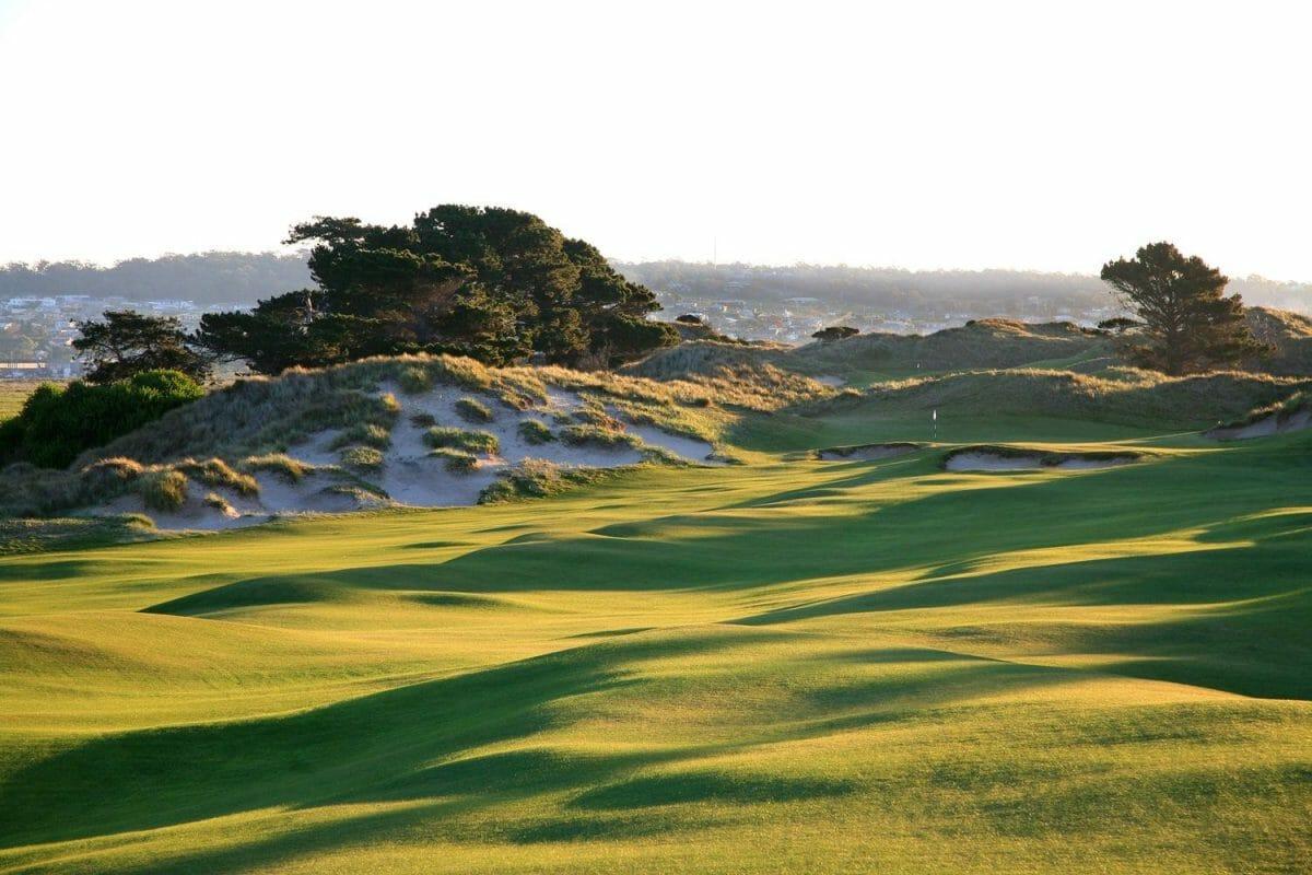 Sunlight casts shadows the golf fairway's undulations