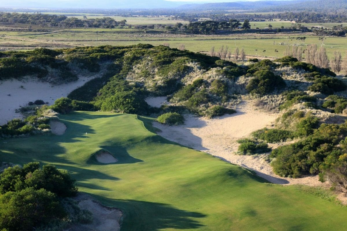 Wide fairway straddled by large sand bunker