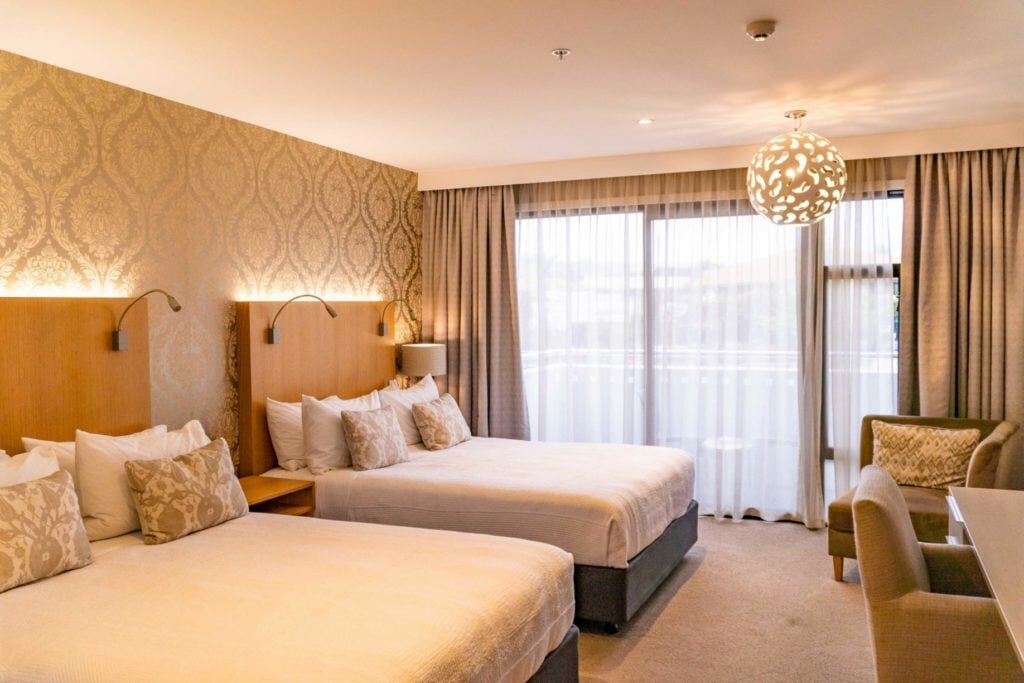 Twin beds inside well lit bedroom at Porters Boutigue Hotel