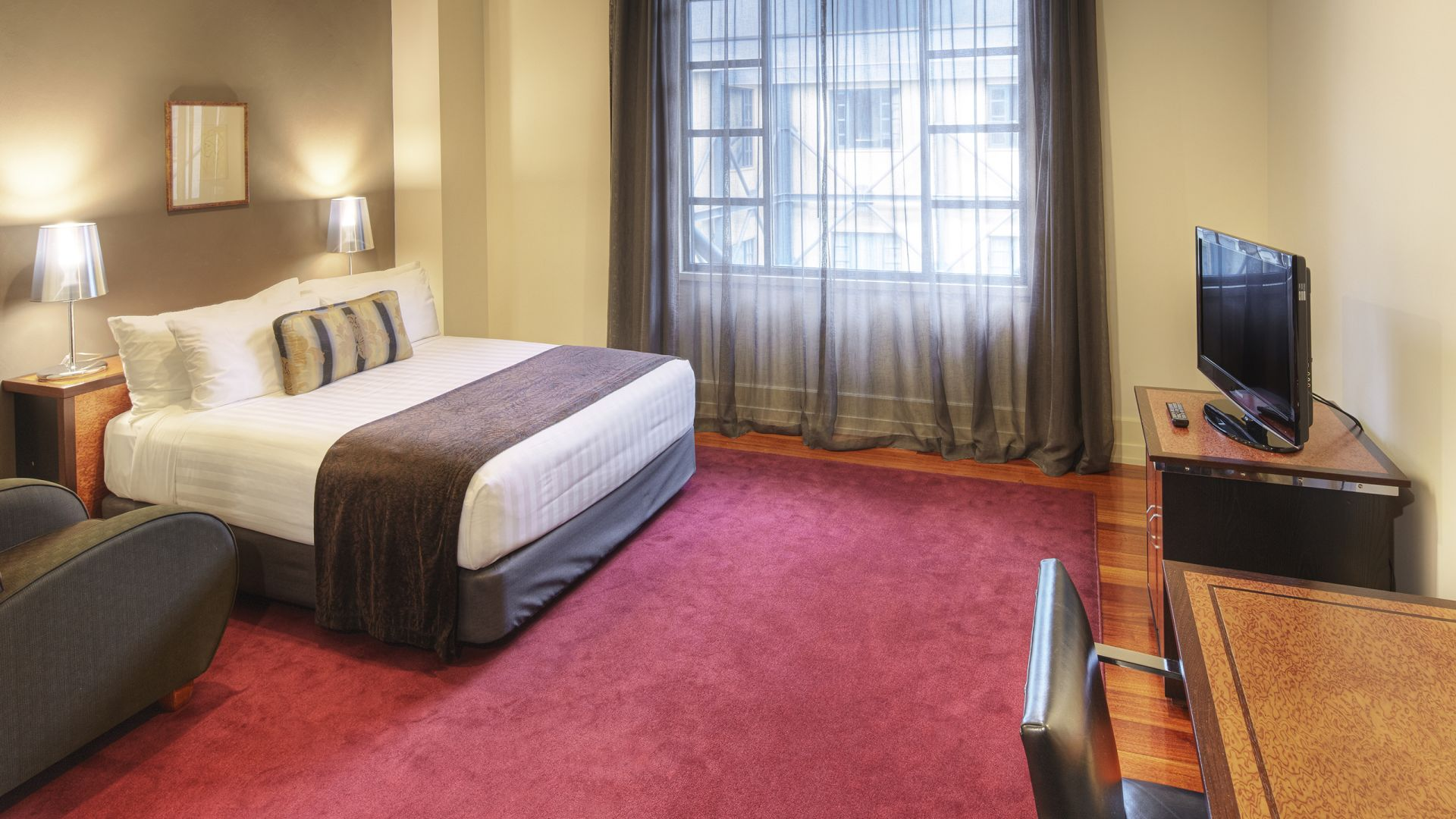Red carpet bedroom and king bed at Heritage Hotel Auckland