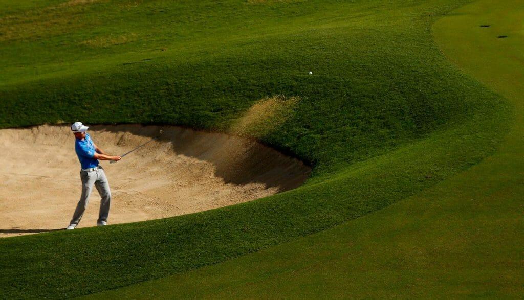 Golfer playing out of bunker at Fiji International golf tournament