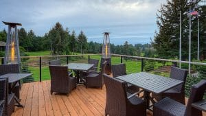 Image of an outdoor patio overlooking the golf course and Pacific Ocean, Salishan Resort, Oregon, USA