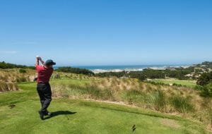 Image of a golfer teeing off at the 15th hole of the golf course, Salishan Resort, Oregon, USA
