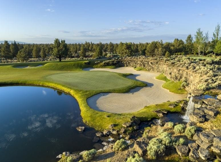 Aerial image of the 13th green surrounded by a lake and bunker, Jack Nicklaus designed Signature Course at Pronghorn Resort, Bend, Oregon, USA