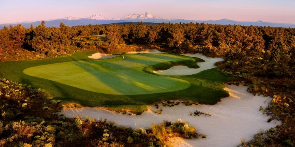 Aerial image of the 1st green and distant Cascade mountain range on the Jack Nicklaus designed Signature course at Pronghorn Resort, Bend, Oregon, USA