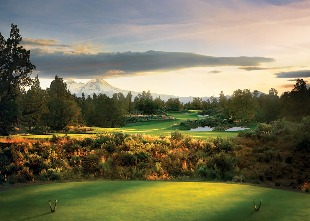 Image of a tee box overlooking a par 3 and distant Cascade mountains on the Jack Nicklaus designed Signature Course at Pronghorn Resort, Bend, Oregon, USA