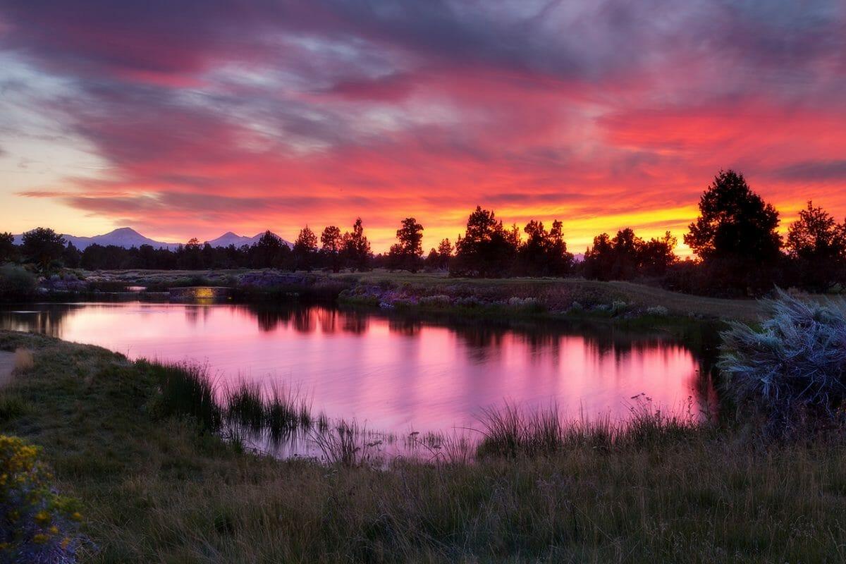 The sun sets over a lake at Pronghorn Golf Resort, Bend, Oregon, USA