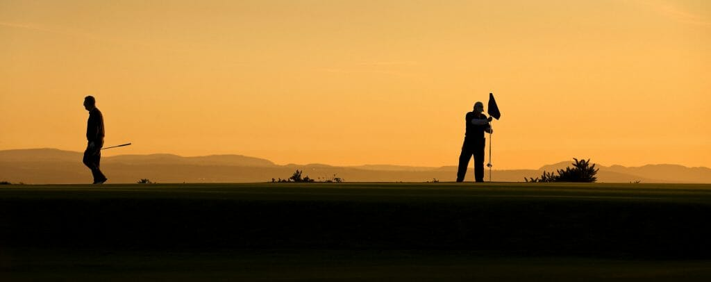 Dusk image of two golfers on the putting green at Fortrose and Rosemarkie golf Links, Inverness, Scotland