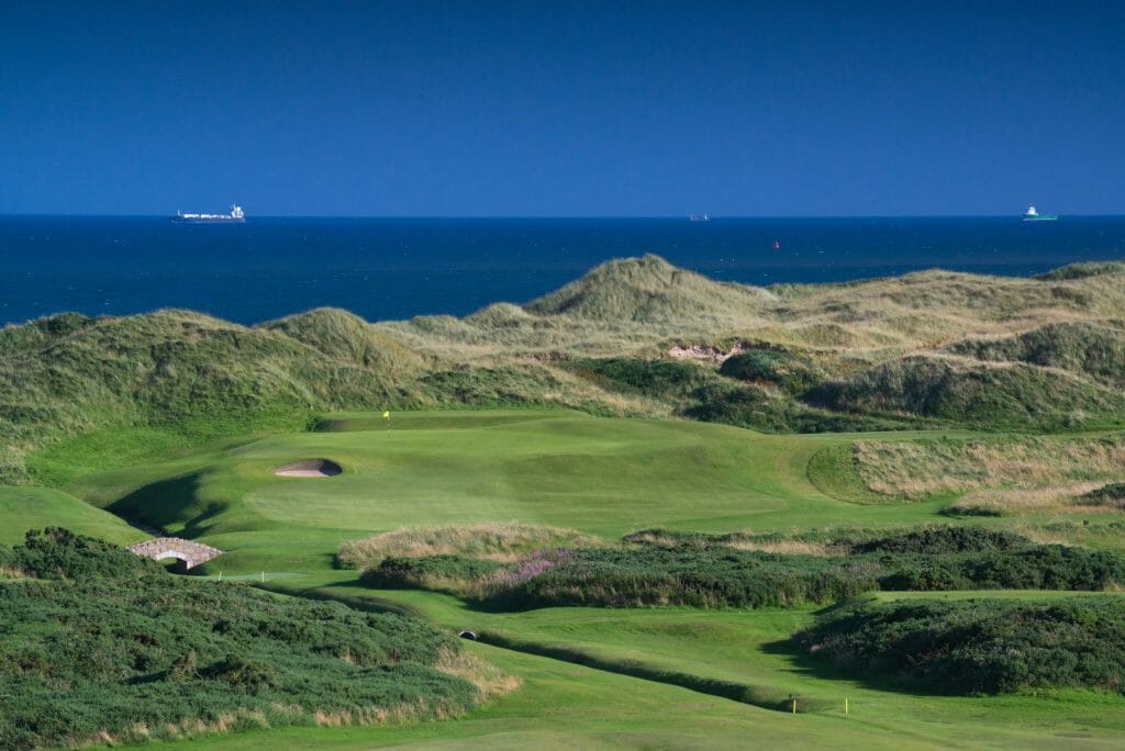 Image of the Golf Course and North sea with a ship on the horizon at Cruden Bay Golf Course, Scotland