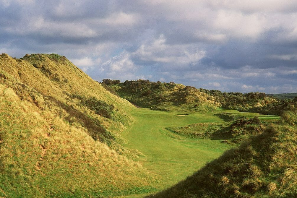 Image displaying a large dune and golf green in the distance at Portsteward Golf Club, Northern Ireland