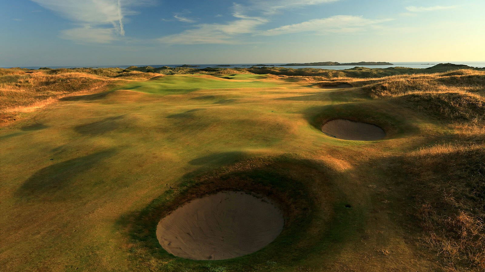 Aerial view of the 2nd green and deep pot bunkers with long shadows at Royal Portrush Dunluce Golf Course, Portrush, County Antrim, Northern Ireland