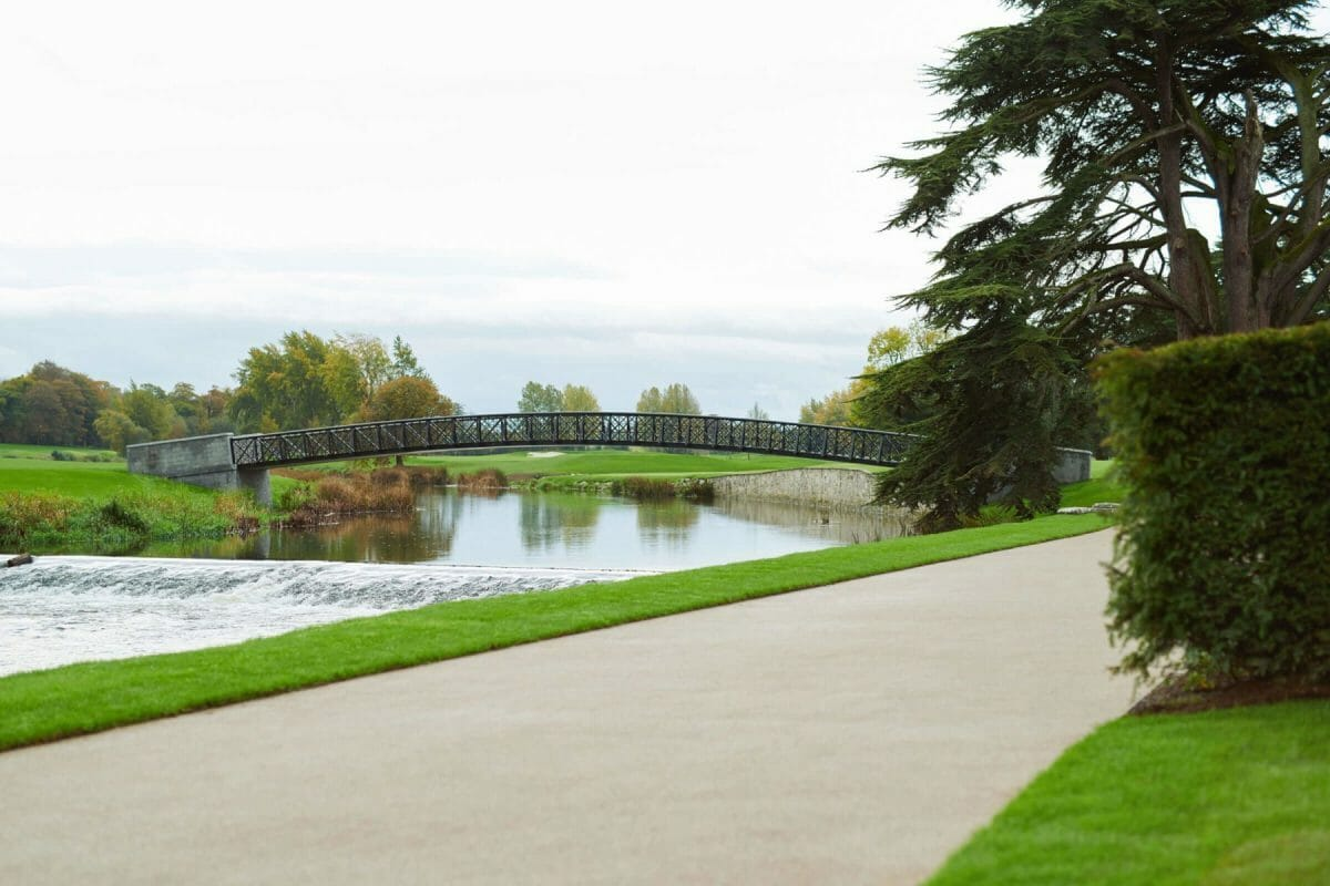 Image depicting a wide bridge over the river along viewed from a pathway at Adare Manor, County Limerick, Ireland, Europe