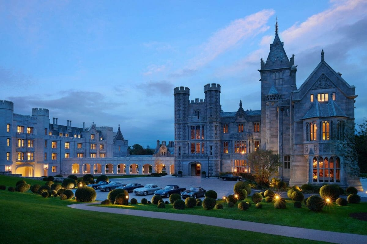 Twilight image of vintage cars parked outside the manor entrance at Adare Manor, County Limerick, Ireland, Europe