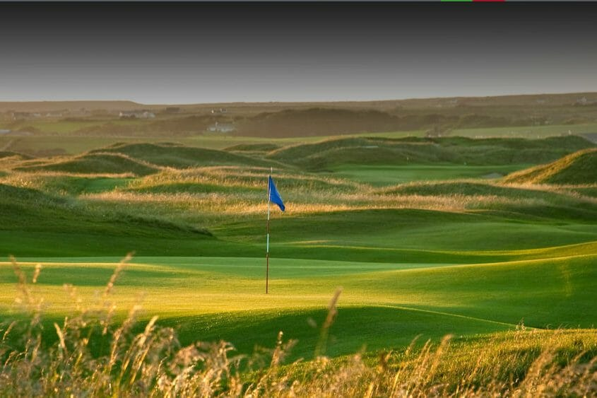 Image displaying the 3rd hole with blue flag sticking out on the Castle Golf Course at Lahinch Golf Club, County Clare, Ireland