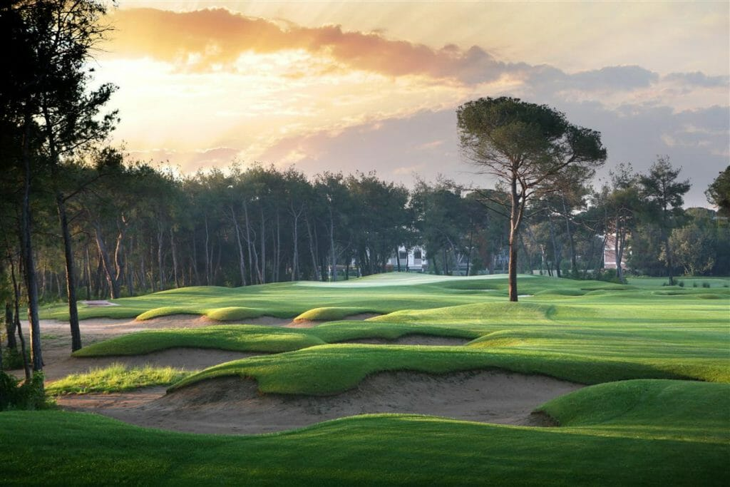 Image displaying the sun setting over undulating bunkers and a lone tree at Montgomerie Links Vietnam Golf Course, Da Nang, Vietnam, Asia