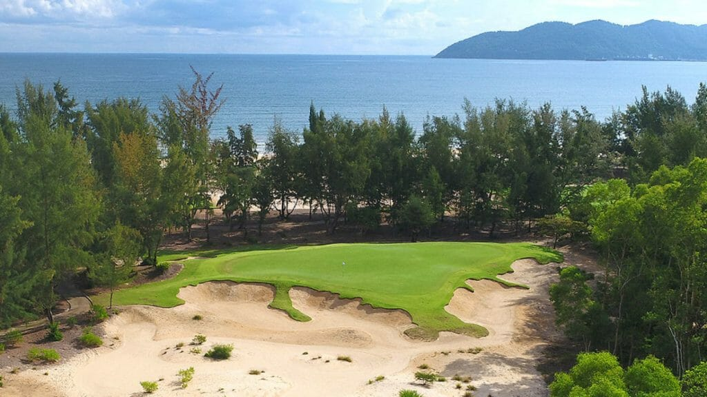 Image of the 6th green with a line of trees separating the golf course from the beach at Laguna Lang Co Golf Club, Da Nang, Vietnam