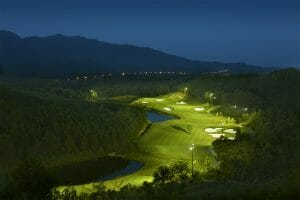 Aerial image of the 11th hole after sunset under floodlights, Ba Na Hills Golf Club, Da Nang, Vietnam