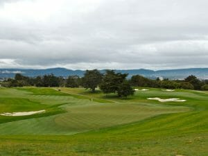 A tiered ninth green overlooks an open fairway at Blackhorse Golf Course