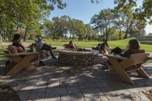 Golfers relax around a firepit at Sentryworld Golf Club