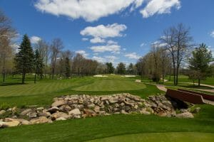 The seventh fairway is separated from the tee by a stone-walled creek at Sentryworld Golf Course