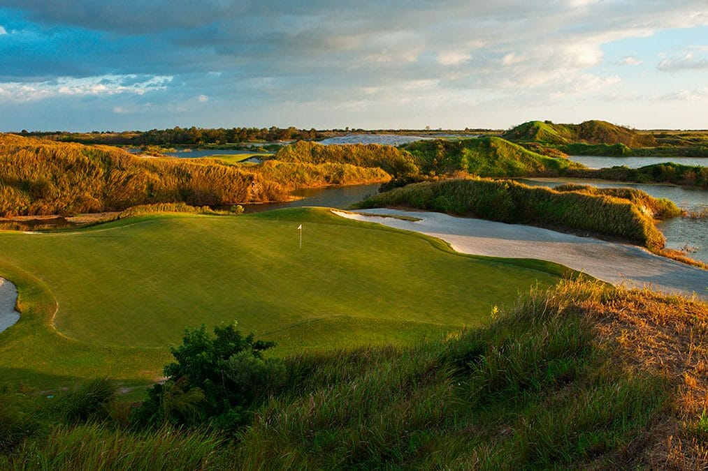 A large green straddled by sand bunkers at dusk on the Red golf Course at Streamsong