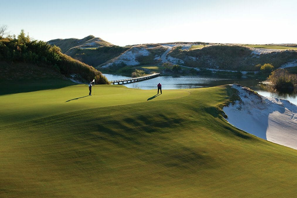 Two golfers putt on the sixteenth green overlooking a lake at Streamsong Golf Resort