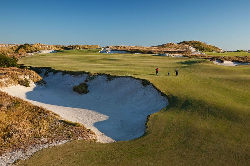 Two golfers play on the fifteenth hole with a large bunker to the left at Streamsong Golf Resort in Florida