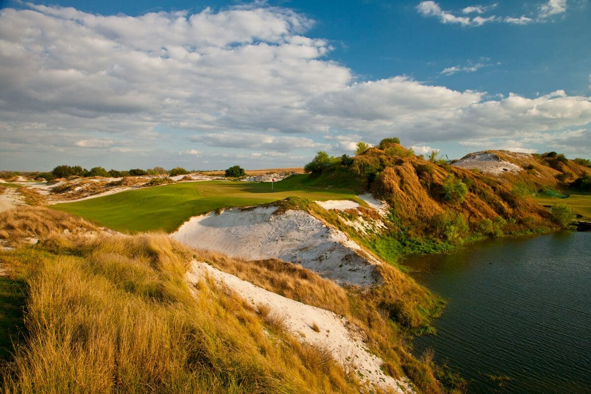 A large raised green leads to a cliff and lake below on the Red Golf Course at Streamsong Resort