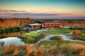 Golden dusk sunlight touches the practice golf facilities and clubhouse at Streamsong Golf Resort in Florida