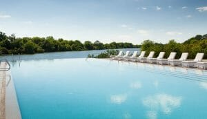 An infinity pool with white lounge recliners overlook a lake at Streamsong Golf Resort in Florida