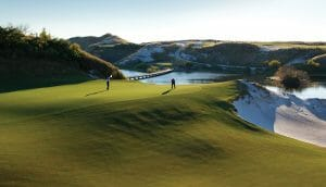 Two golfers putt on the green of the sixteenth hole at Streamsong Resort in Florida