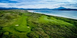 Aerial view of golf greens with fairways and undulating hills on the Old Tom Morris Golf Course at Rosapenna Golf Resort, Ireland