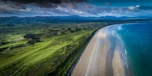 Aerial view of the ocean contrasting with the beach and golf courses at Rosapenna Golf Resort, Ireland