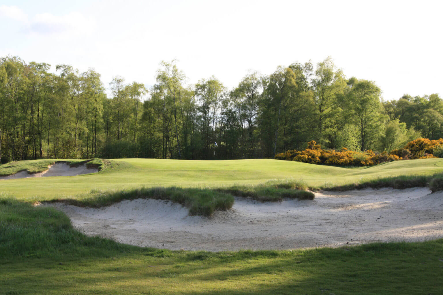 Image of a bunker and first green at Duke's Golf Course