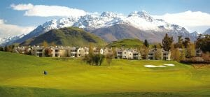 Landscape view of the Millbrook Resort's Golf Course, accommodation and background snow-capped mountains
