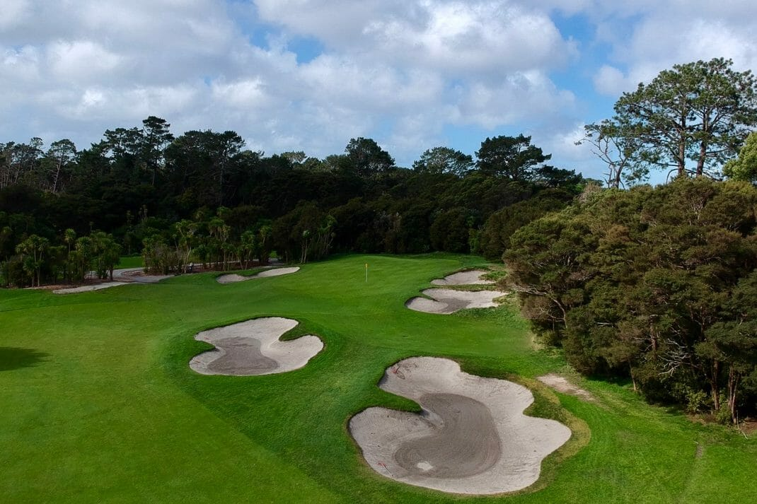 Aerial image overlooking fairway bunkers and the green surrounded by trees at Titirangi golf course