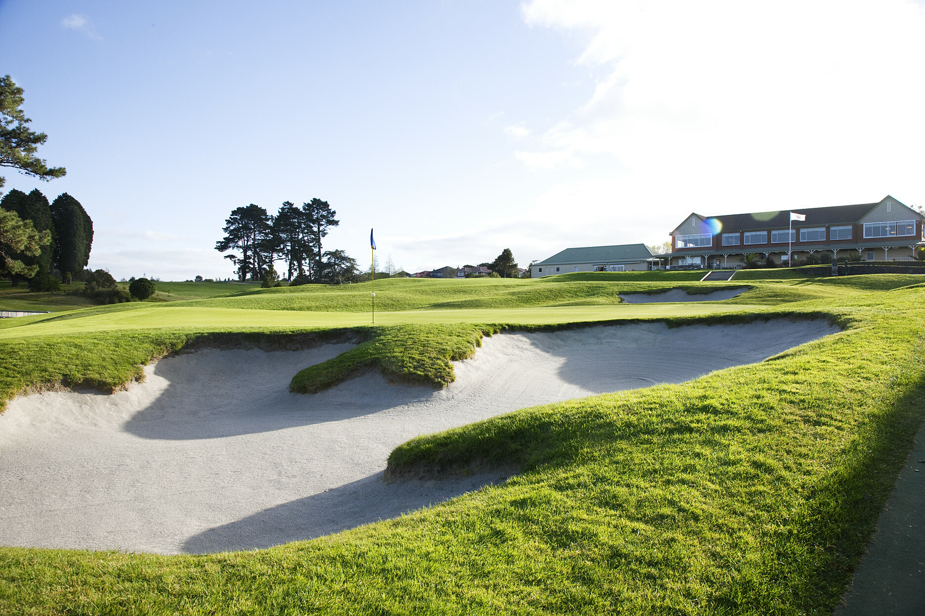 Image displaying the 18th green in the foreground at Titirangi Golf Clubhouse in the background