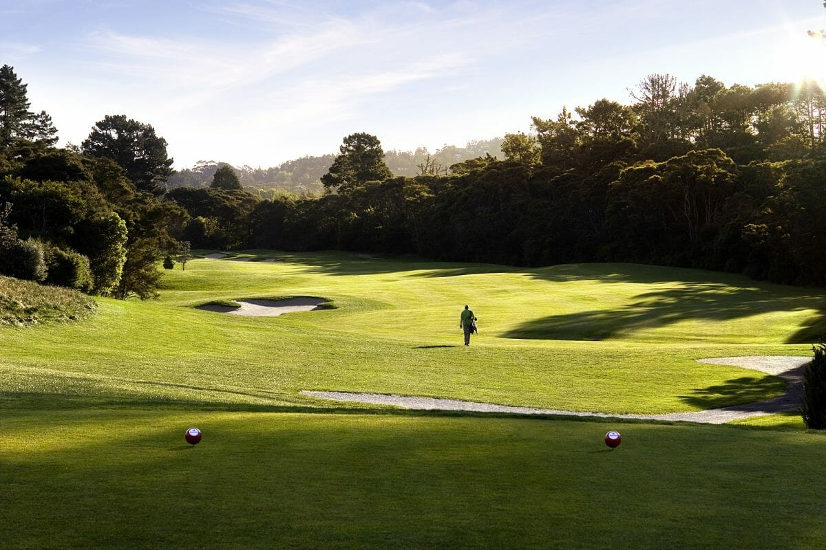 Image of a golfer walking down the 12th hole at Titirangi Golf Course, New Zealand