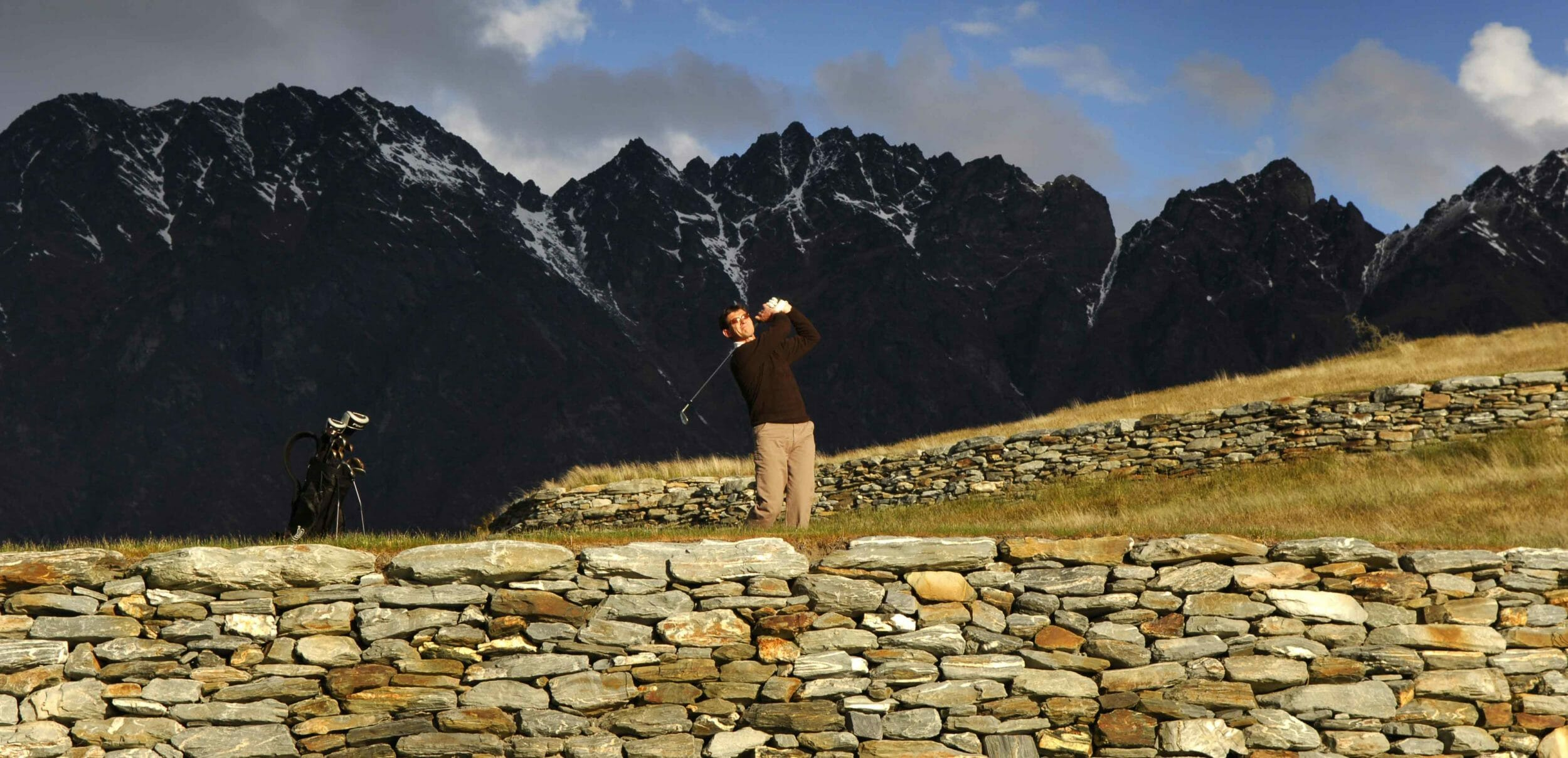 Golfer teeing off at Jack's Point Golf Course near Queenstown, NZ