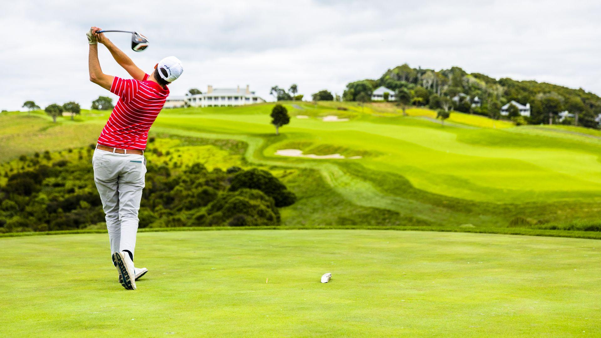 A golfer tee's off at Kauri Cliffs 18th hole, New Zealand's North Island