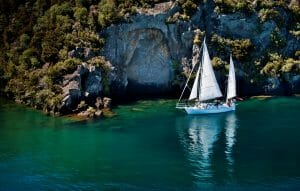 Drone image of Maori rock carvings behind a sail boat on Lake Taupo