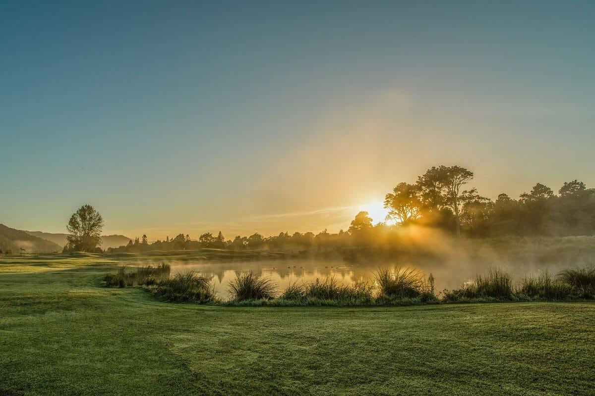 The dawn sun shines through mist over a like on the Royal Wellington Golf Club